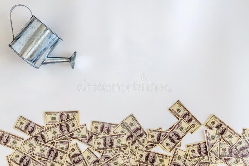 verter-regado de los dólares de los billetes de banco de la regadera en un fondo blanco Concepto, inversión, negocio de lanzamien imagenes de archivo