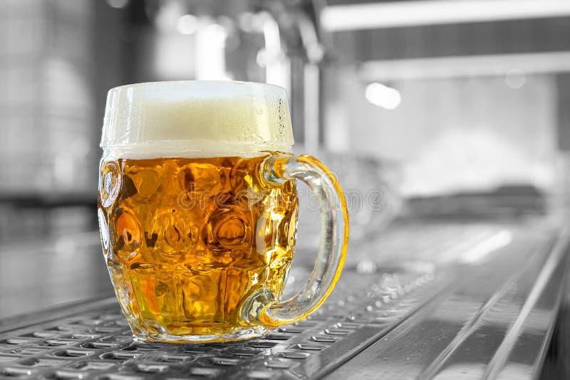 Vertió recientemente la cerveza de cerveza dorada del proyecto en una taza de cristal formada hoyuelos en contador de acero inoxi fotos de archivo