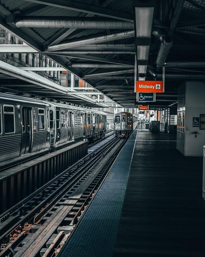 Vertica shot of gray trains in a subway station near platforms royalty free stock photography