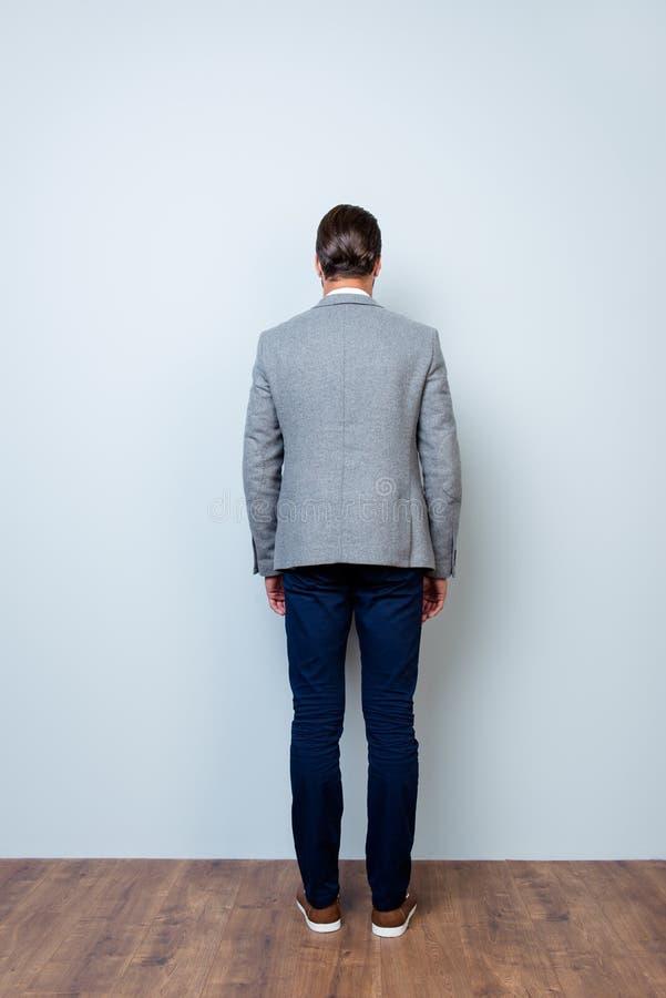 Verticaal achtermeningsportret van gemiddelde lengte van de mens in grijs jasje royalty-vrije stock afbeelding