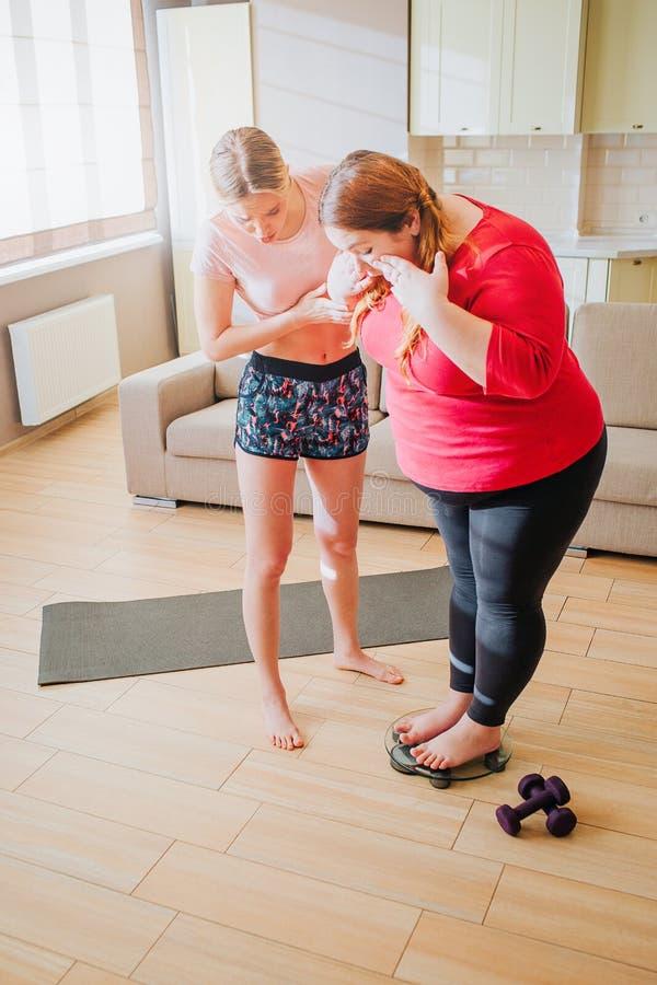 Verticaal beeld van jong slank model die te zwaar meisje helpen om op gewichtsschaal op te staan Neer het kijken Domoren en stock afbeelding