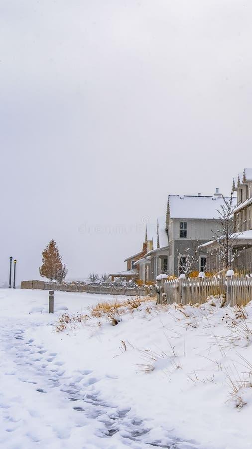 Verticaal die de Winterweer met sleep op de sneeuw naar de huizen in Dageraad wordt gestempeld royalty-vrije stock afbeelding