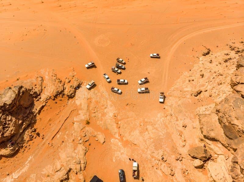 Verticaal die satellietbeeld van een pak off-road voertuigen met toeristen in de Wadi Rum-woestijn in Jordanië, met hommel wordt  royalty-vrije stock fotografie