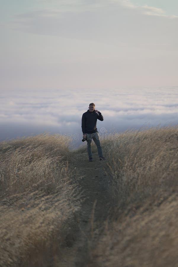 Verticaal die van een mannetje wordt geschoten die de camera bovenop de berg bekijken Tam in Marin, CA stock afbeeldingen