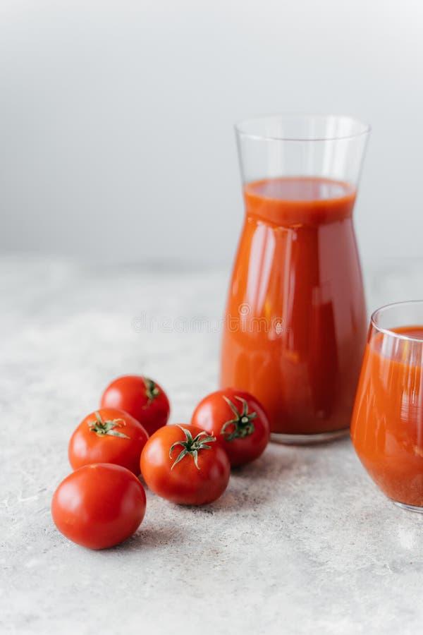 Verticaal die van vers rood tomatesap in glas, rode verse ruwe tomaten dichtbij op witte achtergrond wordt geschoten Het maken va royalty-vrije stock afbeeldingen