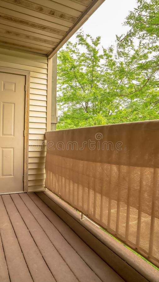 Verticaal frame Balcony of a home with white wall siding and view of bomen against white sky royalty-vrije stock foto's