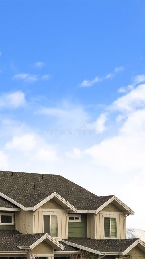 Verticaal Huis buiten met mening van het donkere geworpen dak tegen een bewolkte blauwe hemel stock afbeelding
