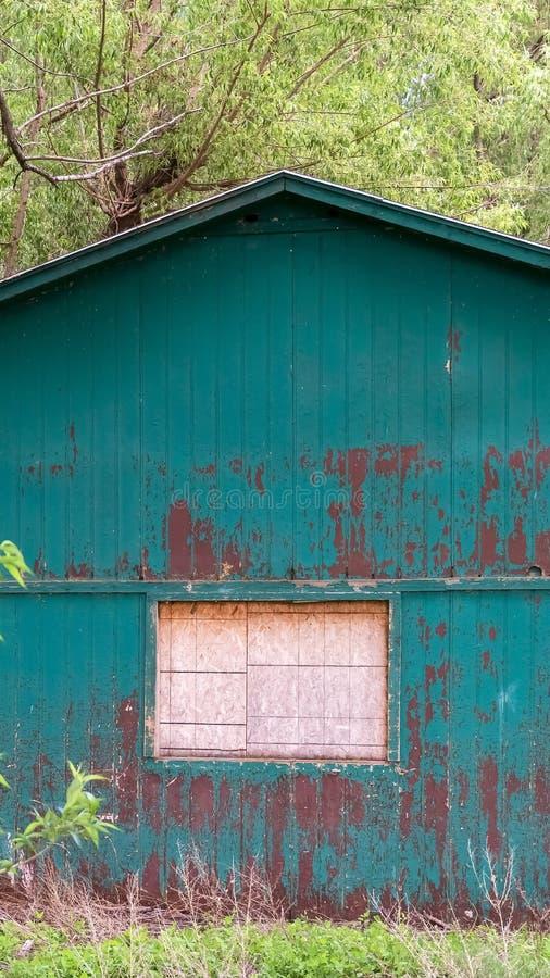 Verticaal kader Buiten van loods in het bos met wit venster en schil groene verf op muur stock foto