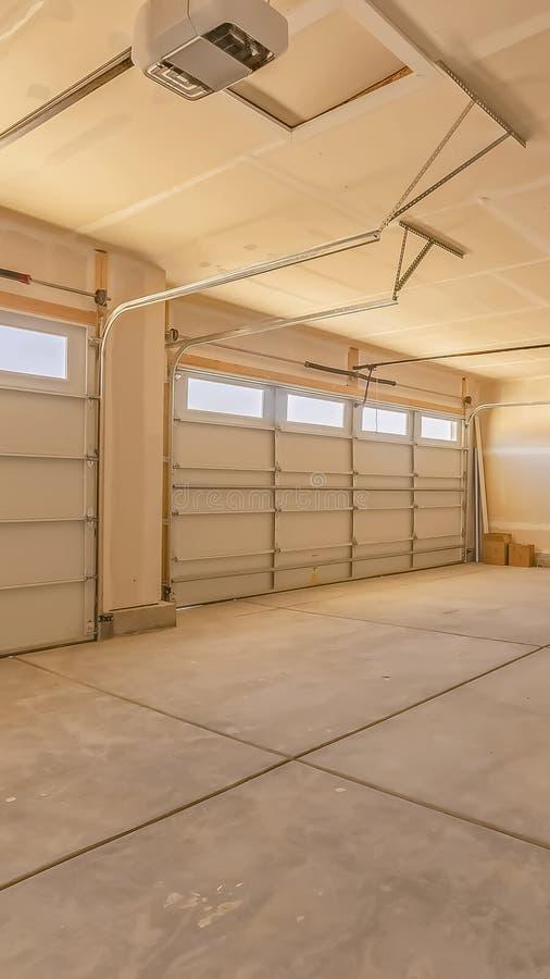 Verticaal kaderbinnenland van een lege garage met twee grote deuren en kleine rechthoekige vensters stock foto