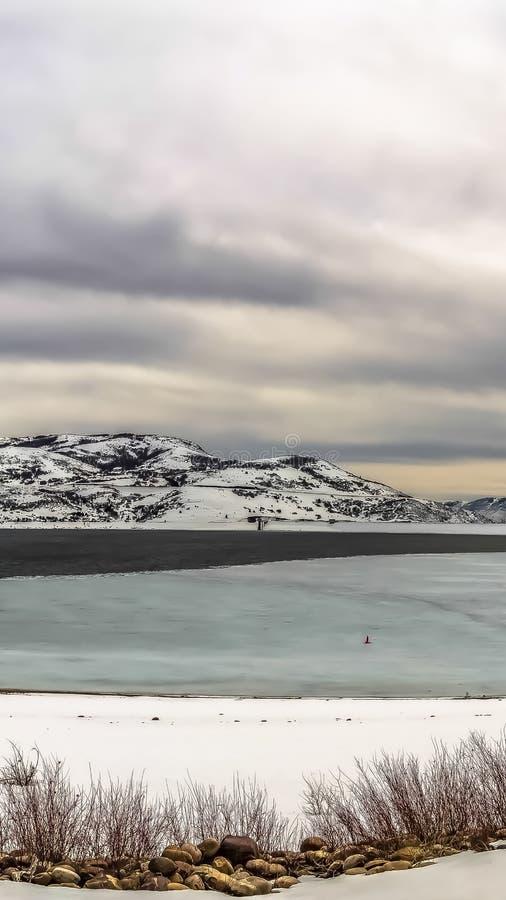 Verticaal kaderpanorama van een bevroren meer en een sneeuwberg onder bewolkte hemel in de winter stock foto