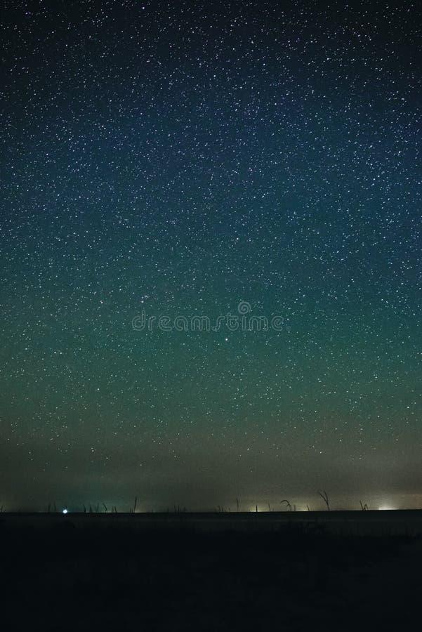Verticaal landschap van heldere sterrige nachthemel met lichten op op het en zandig leeg strand met gras en oceaan stock afbeelding