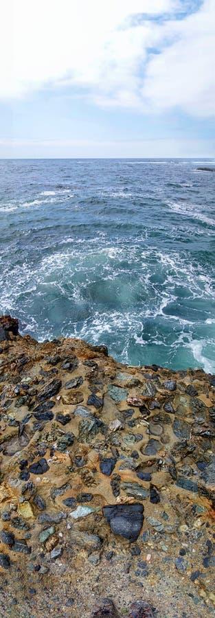 Verticaal panorama van het rotsachtige richel teruglopen in de oceaan royalty-vrije stock afbeeldingen