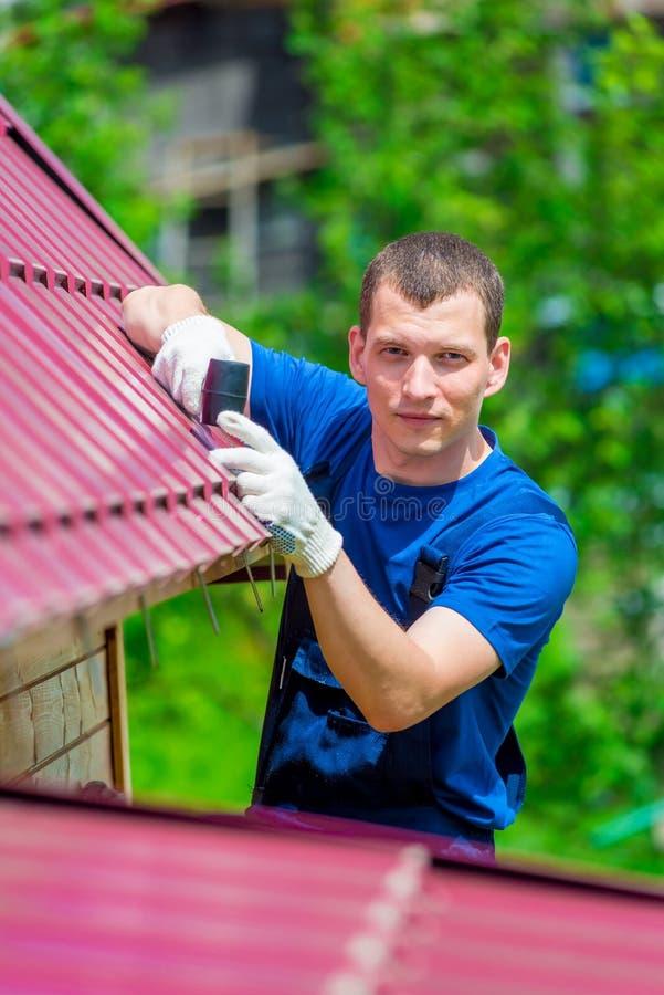 verticaal portret van een mens met een hamer die het dak van het huis herstellen stock afbeelding