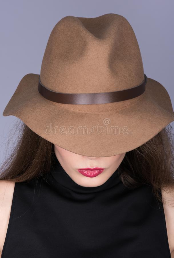 Verticaal portret van een vrouw in een bruine hoed en zwarte kleding met haar haar stock afbeelding