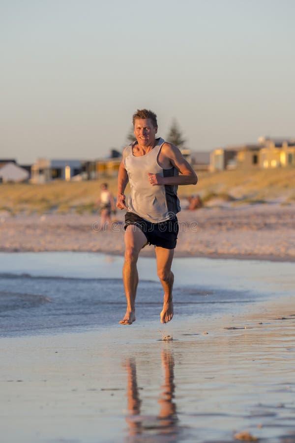 Verticaal portret van jonge atletische geschikte en sterke agentmens opleiding op het strand van de de Zomerzonsondergang in over stock foto's