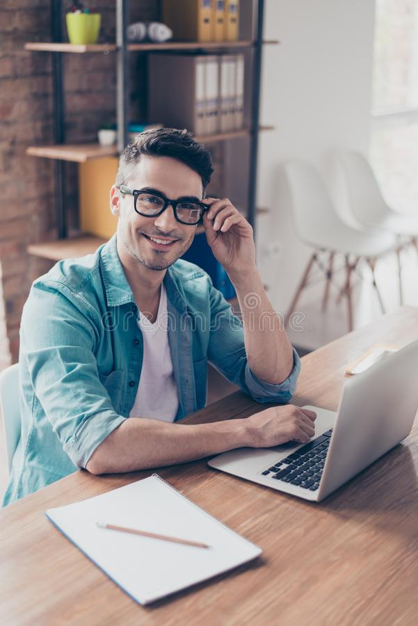 Verticaal portret van jonge zakenman in jeansoverhemd en glasse stock afbeeldingen