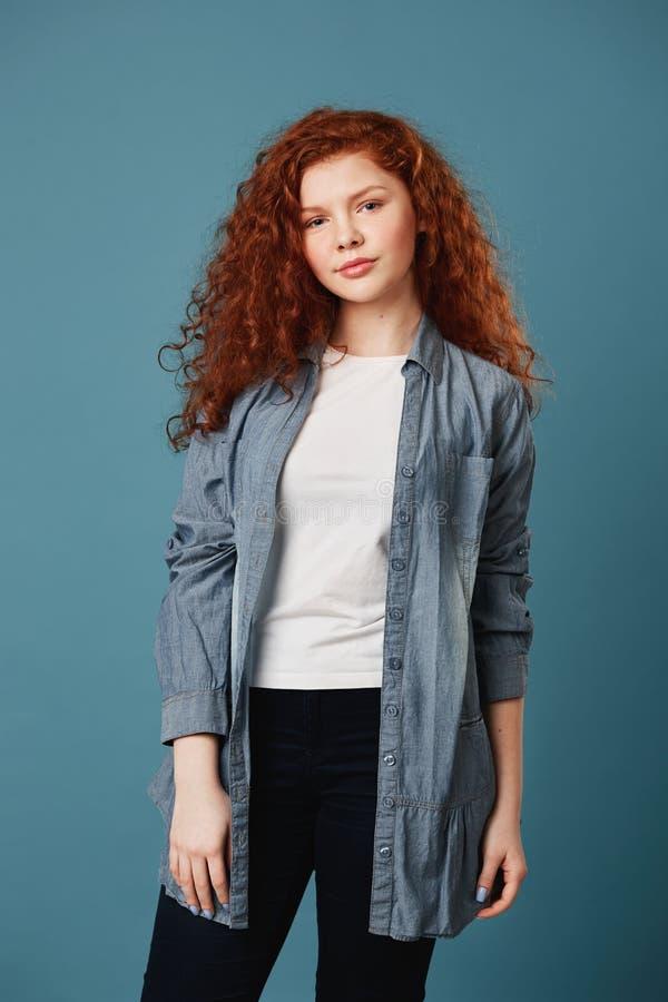 Verticaal portret van knap tienermeisje met golvend gemberhaar en sproeten in witte t-shirt en het grijze cardigan stellen royalty-vrije stock foto