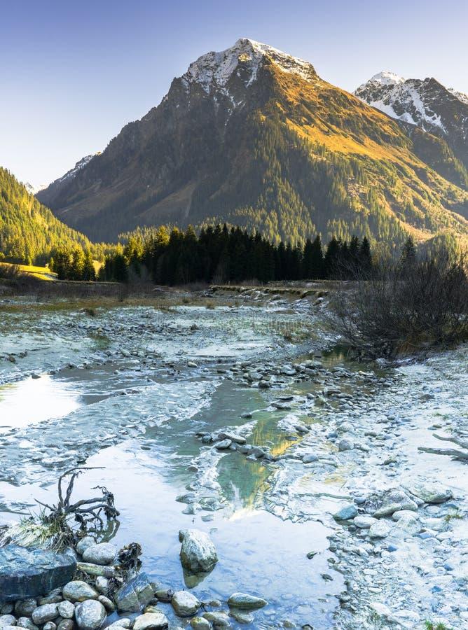 Verticaal rotsachtig berglandschap in de vroege winter met snow-capped pieken en kleurrijk bos en een bergstroom in foregrou stock afbeeldingen