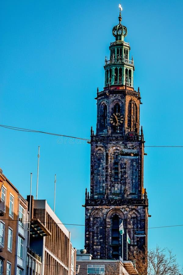 Verticaal schot van een mooie lange kloktoren onder heldere blauwe hemel in Groningen, Nederland royalty-vrije stock foto's