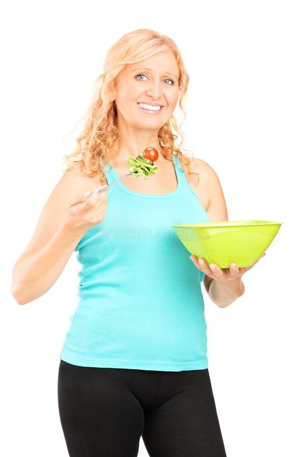 Verticaal van een rijpe dame wordt geschoten die een salade eten die stock fotografie