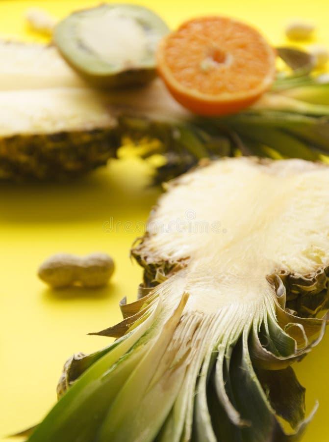 Verticaal van rijpe natuurlijke ananas wordt geschoten, orsnge, kiwi op heldere zonnige oppervlakte die royalty-vrije stock fotografie