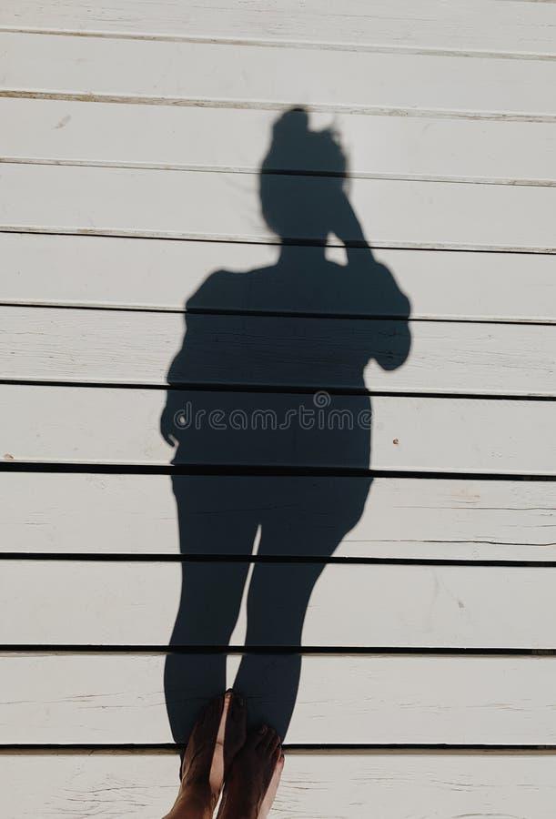 Verticaal van wijfjesvoeten en haar schaduw op een wit houten platform wordt geschoten dat stock foto