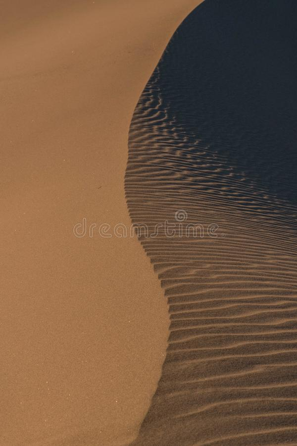 Vertical abstract shot of the water reaching the sand of the beach leaving trails. A vertical abstract shot of the water reaching the sand of the beach leaving royalty free stock image