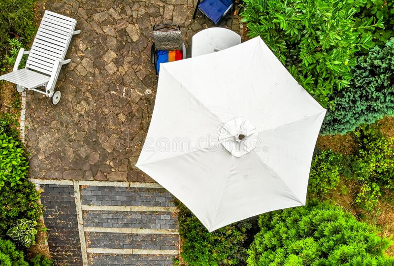 Vertical aerial photograph of a bright parasol on a terrace, taken from close up with the drone. stock photography