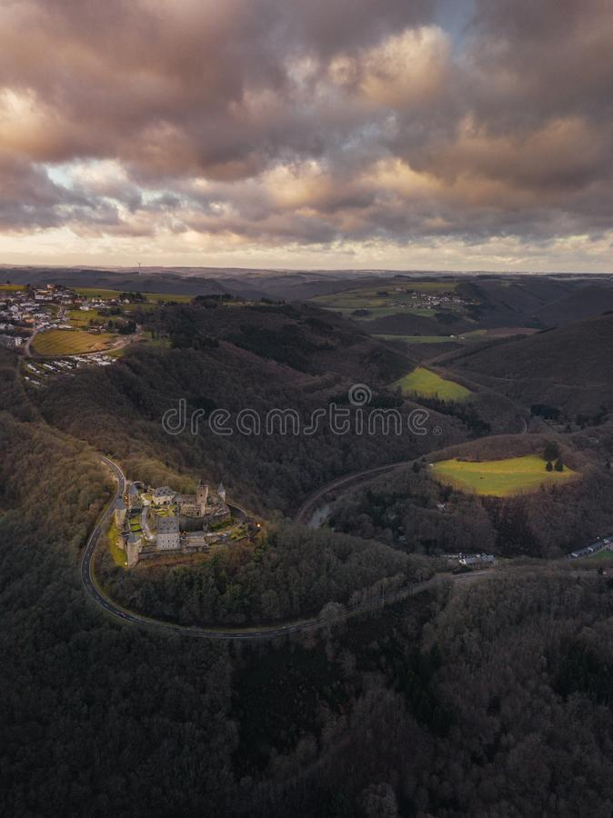 Vertical aerial shot of a castle surrounded by trees on hills under a pink cloudy sky. A vertical aerial shot of a castle surrounded by trees on hills under a royalty free stock photos