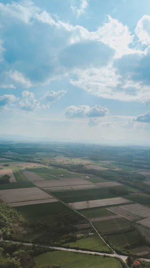 Vertical aerial shot of grassy fields under a cloudy sky. A vertical aerial shot of grassy fields under a cloudy sky stock images