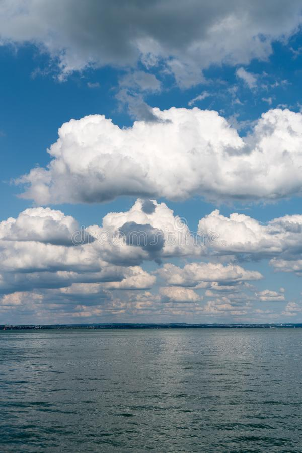 Vertical background of flat anvil-like cumulus clouds in blue sky and blue lake below. Vertical background of flat anvil-like cumulus clouds in blue sky over royalty free stock photography