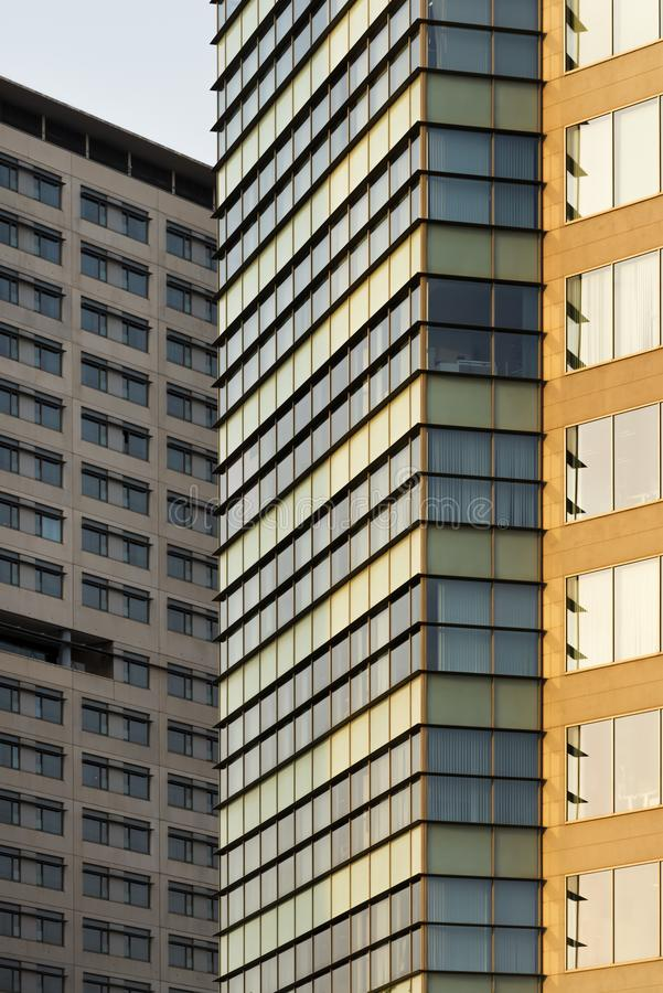Vertical background of overlapping concrete facades. Vertical composition with a close-up of facades of concrete buildings, which have dull colors, to use as royalty free stock photo