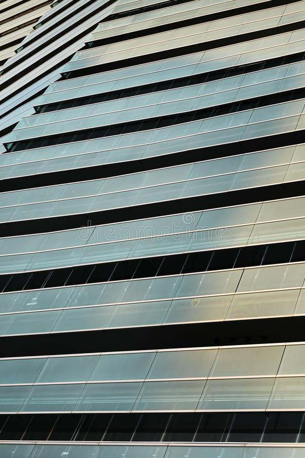 Vertical background of overlay glass facades. Close-up of an overlapping of glass facades that reflect the colors of the sky at sunset, the lines of the stock photography