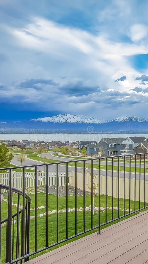 Vertical Balcony with wooden floor and metal railing overlooking lake and mountain. Houses along a curving road can also be seen under the striking cloudy blue royalty free stock image