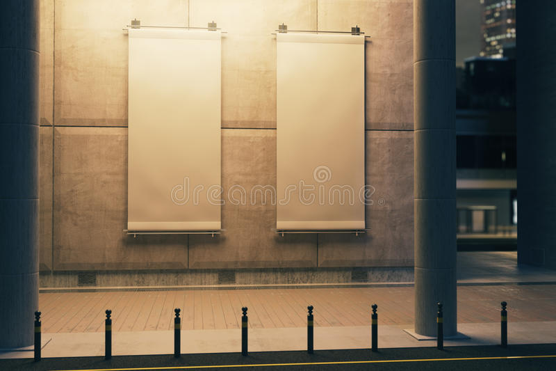 Vertical banners on building, nighttime. Two blank illuminated vertical banners hanging on concrete building. Nighttime. Ad concept. Mock up, 3D Rendering royalty free illustration