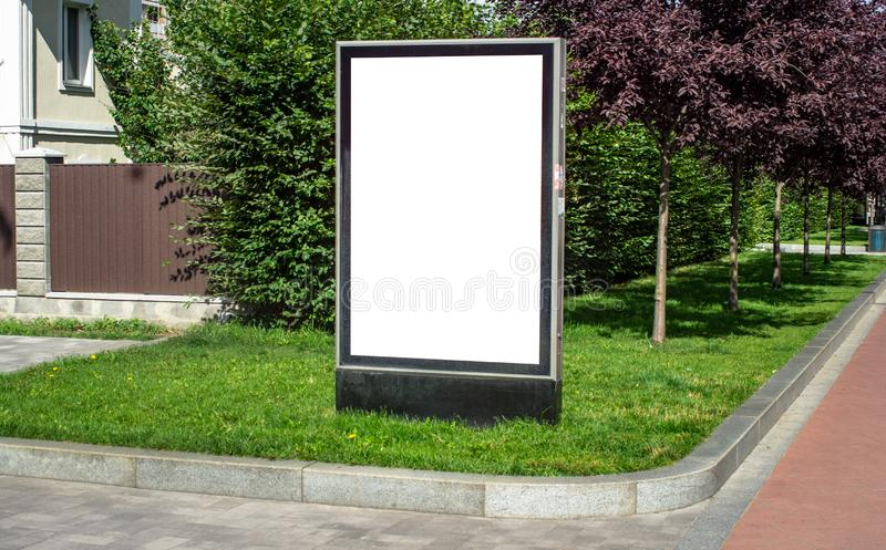 Vertical billboard or citylight outdoor. Vertical billboard or citylight blank on the grass outdoor town street sunny day royalty free stock photo