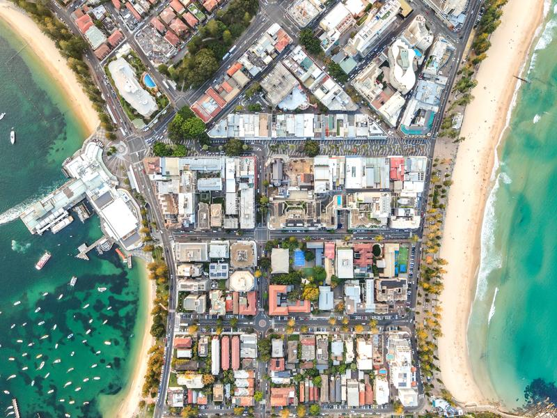 Vertical bird`s eye aerial drone panoramic view of the oceanside suburb of Manly, Sydney, New South Wales, Australia. Harbourside on the left, oceanside with stock photos