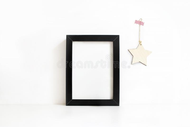 Vertical black blank wooden frame mockup on white table. Wooden star decoration hanging on the wall. Styled stock stock photo