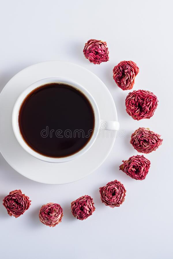 Vertical black coffee in white Cup with saucer decorated with rose buds on white background, art coffee concept. Vertical top view black coffee in white Cup with stock image