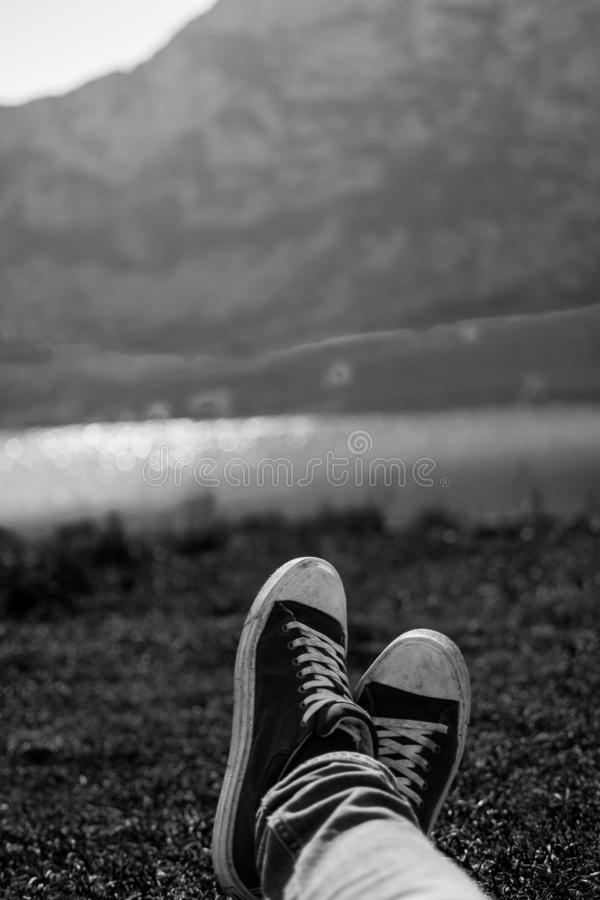 Vertical black and white close-up of a pair of shoes relaxing on a meadow with a defocused lake in the background.  royalty free stock photo