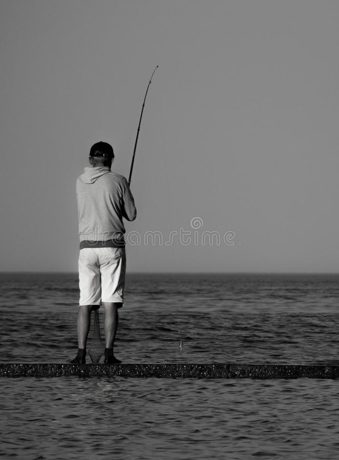 Vertical black and white photo of a lone fisherman standing on a concrete pier in the sea stock photo