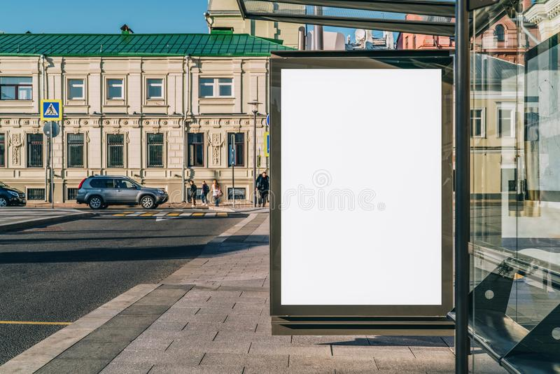 Vertical blank billboard at bus stop on city street. In background buildings, road. Mock up. Poster next to roadway. stock photo