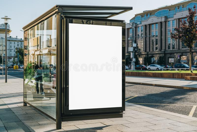 Vertical blank billboard at bus stop on city street. In background buildings, road. Mock up. Poster next to roadway. stock image