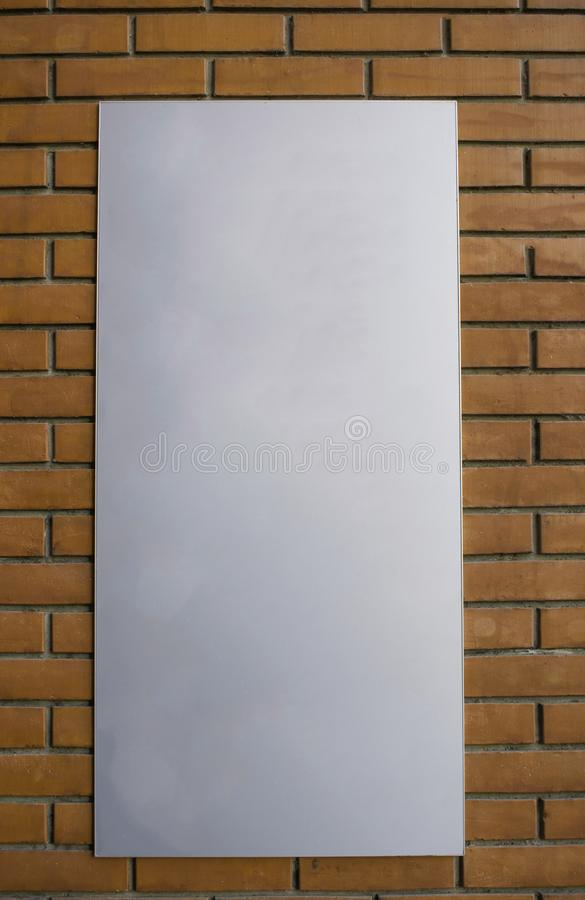 Vertical blank billboard on a red brick wall. Vertical gray blank billboard on a red brick wall stock photo