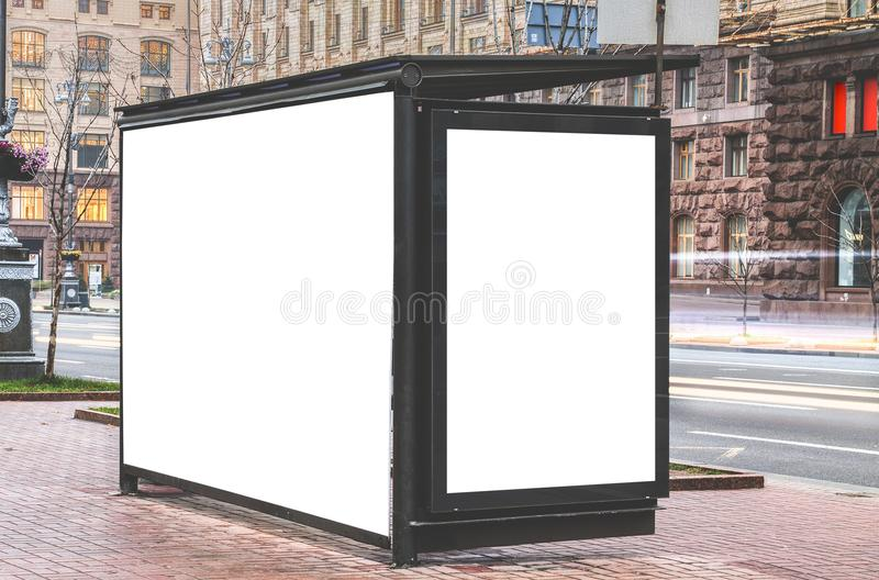 Vertical blank glowing billboard on the bus stop. Street outdoor advertising royalty free stock photography