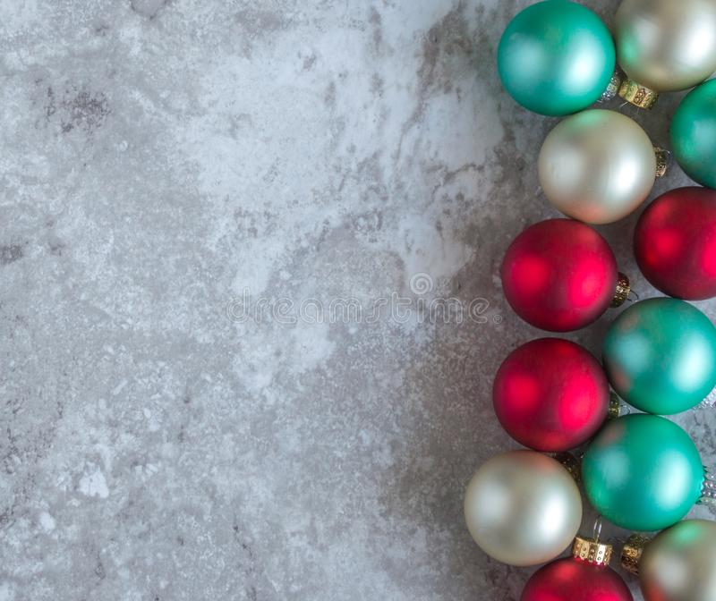 Vertical border of Christmas ornaments. Vertical border of colorful Christmas ornaments on a gray marble counter top with copy space stock images