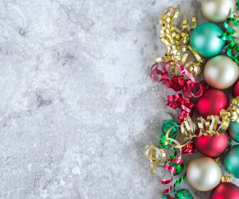 Vertical border of Christmas ornaments and curling ribbon. Vertical border of colorful Christmas ornaments and curling ribbon on a gray marble counter top with royalty free stock image