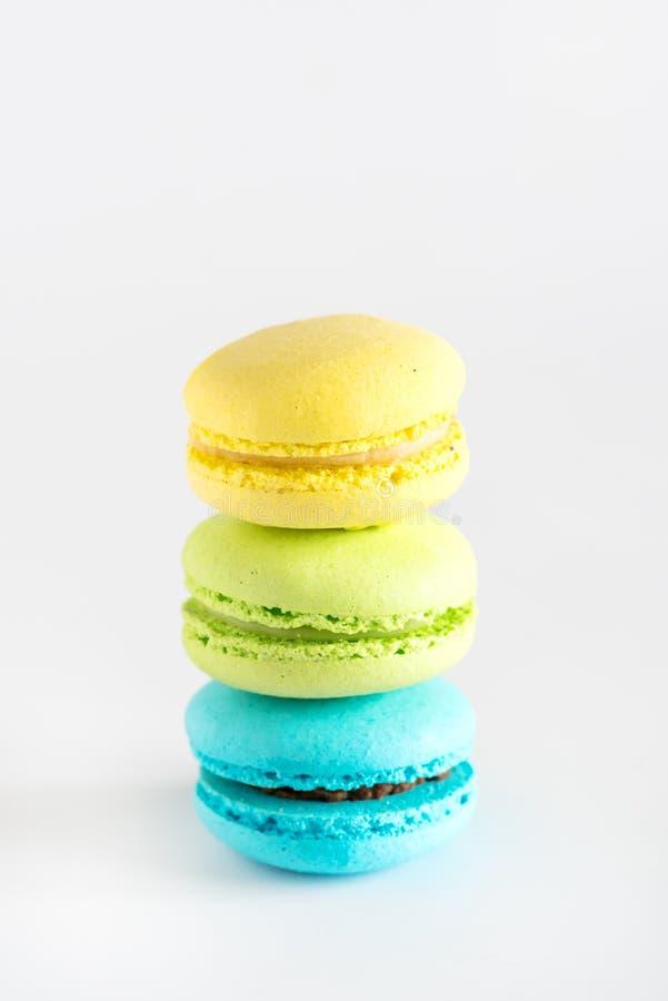 Vertical branco saboroso do fundo de Macarons da sobremesa francesa amarela colorida de Macarons do verde azul de Macarons foto de stock