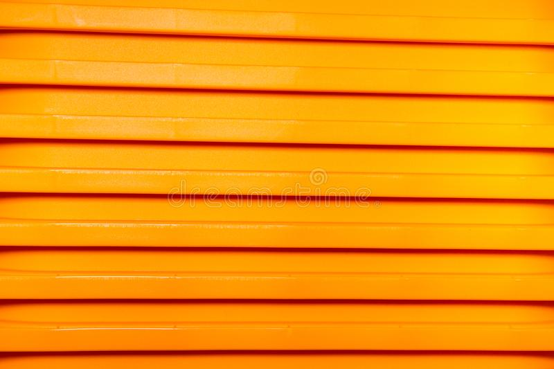 Vertical bright stripes of plastic basins stacked in a pile of yellow. Abstraction, structures, royalty free stock photos