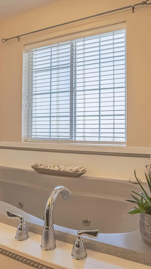 Vertical Built in bathtub and wall mounted towel rack inside a bathroom with beige wall. Bathroom ornaments and windows with blinds can also be seen inside stock images